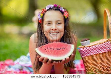 Happy smiling child eating watermelon outdoors in park