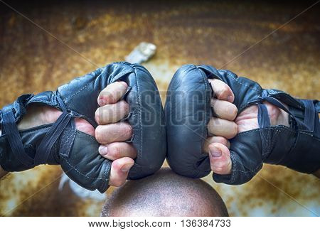 Two hands clenched in a fist in for boxing gloves lie on the head
