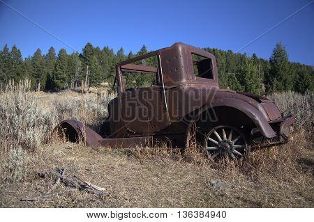 An antique jalopy, abandoned in the mountains.