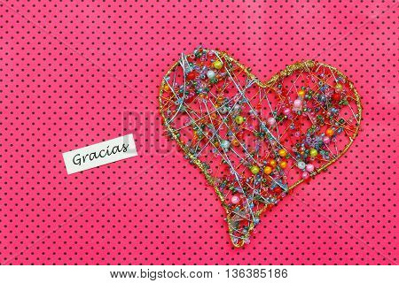 Gracias (thank you in Spanish) card with heart made of colorful beads on dotty pink surface