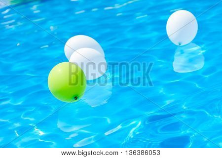 The balloons swimming in the summer pool. Poolside party. The balloons on water.