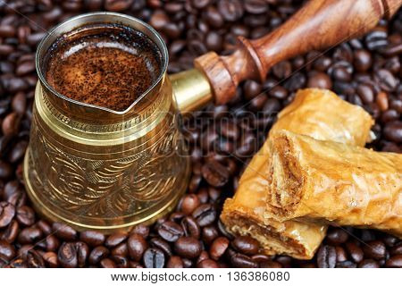 Baklava and hot black coffee in a traditional coffee pot