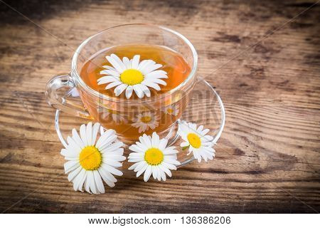 Herbal tea with chamomile flowers on old wooden table