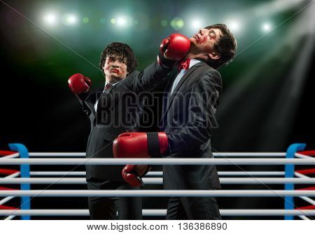 Two businessman in boxing gloves in ring fighting with each other