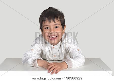 the boy sits at a table and smiles