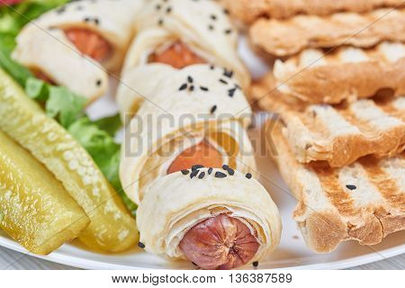 Sausages baked in a puff pastry on a plate