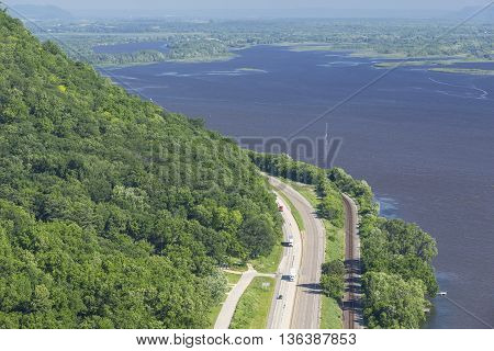 A scenic view of the Mississippi River with semi trucks and a car on the highway.