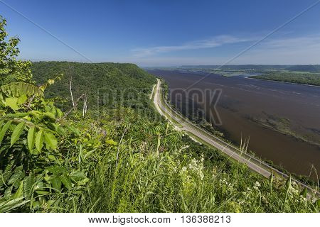 A scenic view of the Mississippi River with road and railroad tracks.