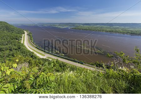 A scenic view of the Mississippi River with a passenger train traveling below.