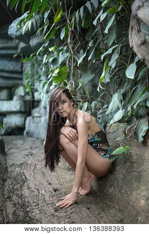 Stylish girl with loose hair squats on the toes near the stone wall with green plants. She wears a colorful swimsuit with pictures. Her right hand is on the left knee, left hand is on the ground. Hairstyle hides her right eye.