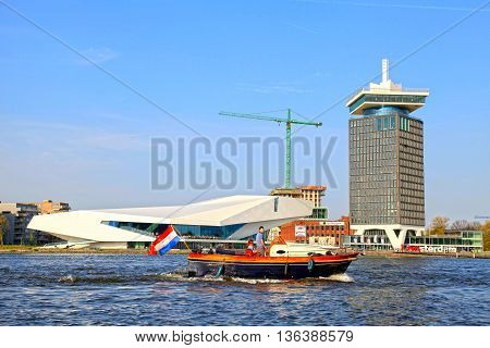 AMSTERDAM, NETHERLANDS - MAY 6, 2016: People in a boat and EYE Film Institute and Overhoeks Tower in Amsterdam, Netherlands. EYE Film Institute includes a cinematography museum.