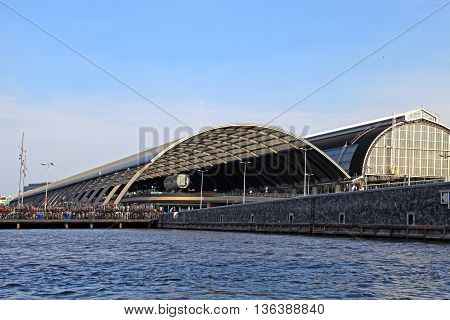 AMSTERDAM, NETHERLANDS - MAY 6,2016: Building exterior of Amsterdam Central Station Amstel river and blue sky, Amsterdam, Netherlands.