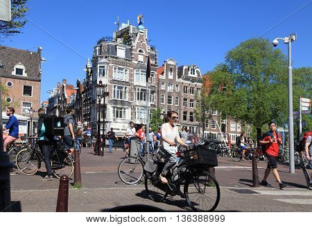 AMSTERDAM, NETHERLANDS - MAY 8, 2016: Local people on bicycle in historical center in Amsterdam, the Netherlands. Bicycles outnumber people in Amsterdam: 760000 citizens and nearly a million bikes.