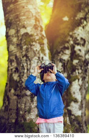 Young boy in a blue coat looking through binoculars in the forest