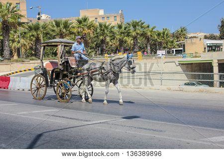 VALETTA MALTA - SEP 24 2012: typical horse coach rider in Valetta on a public street.