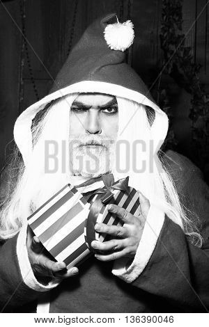 New year man with serious face with long beard and hair in santa claus christmas coat holding present box black and white