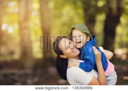 Loving son hugging his happy mother in park