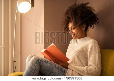 Girl relaxing while reading a book at home.