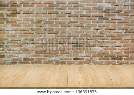 Wood floor with background of grunge red brick wall