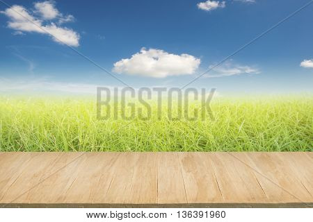 Wood floor with background of green grass field