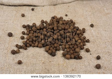 Aromatic allspice pepper seed on sack cloth