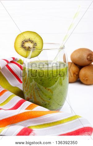 Glass of fresh kiwi juice on white wooden background selective focus