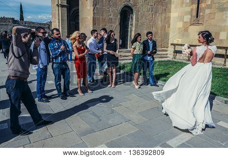 Mtskheta Georgia - April 26 2015. Bride poses photo in front of Svetitskhoveli Cathedral (english - Cathedral of the Living Pillar) in Mtskheta one of the oldest cities of Georgia