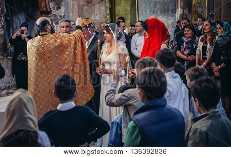 Mtskheta Georgia - April 26 2015. Orthodox priest puts corwn on groom's head during traditional wedding ceremony in Svetitskhoveli Cathedral (english - Cathedral of the Living Pillar) in Mtskheta one of the oldest cities of Georgia