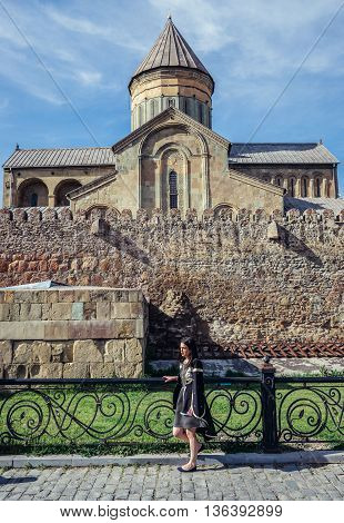 Mtskheta Georgia - April 26 2015. Young woman stands in front of Svetitskhoveli Cathedral (english - Cathedral of the Living Pillar) in Mtskheta one of the oldest cities of Georgia