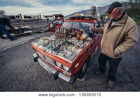 Mtskheta Georgia - April 26 2015. Man shows souvenirs for sale on the hood of his old Lada car in front of the Holy Cross Monastery of Jvari near Mtskheta one of the oldest cities of Georgia