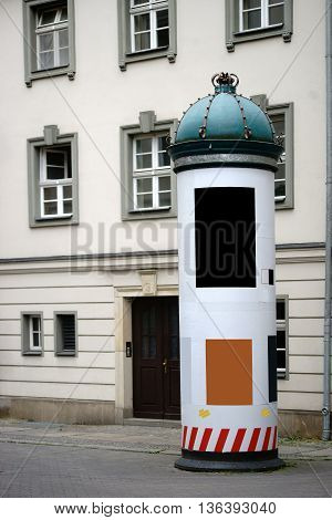 An advertising pillar with posters and signs in downtown Berlin and with a bent crown on the top.