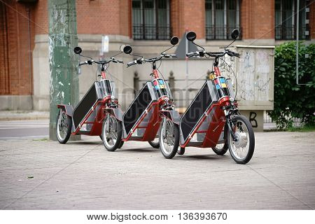 Bicycles or tricycles standing next to each other for hire.