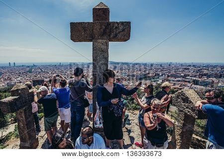 Barcelona Spain - May 26 2015. Tourists takes photos of Barcelona skyline seen from Three Crosses Hill in Park Guell