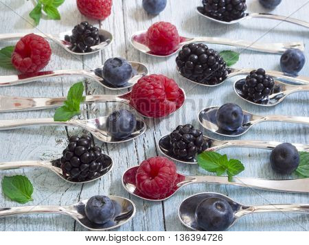 raspberries, blueberries and blackberries on the little spoons with mint leaves