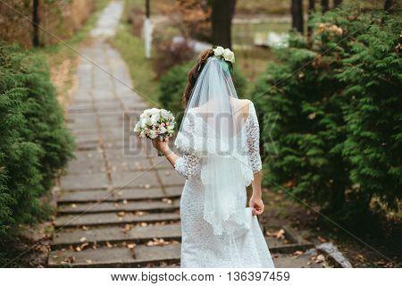 Bride walks holding wedding bouquet in her hands