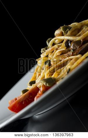 Tilted angle close up view of a plate of traditional Italian spaghetti with capers and tomatoes over a dark background with copy space.