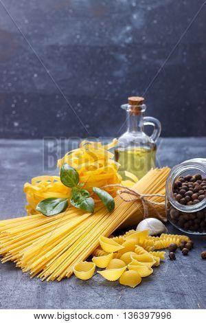 Italian food pasta ingredients basil olive oil garlic cheese on a dark background