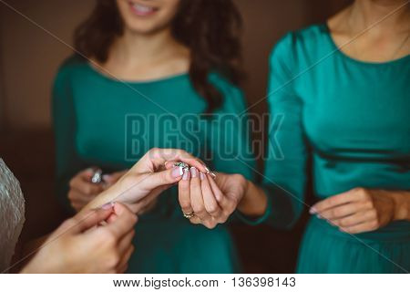 Closeup bride is getting ready in the morning with bridesmaids