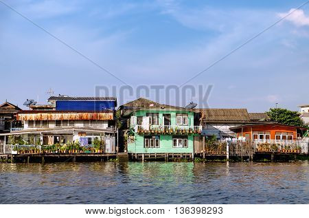 Old Chao Phraya River Thai traditional houses village riverfront in Bangkok Thailand.