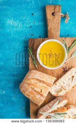Mediterranean snacks set. Olive oil, herbs and sliced ciabatta bread on rustic wooden board over blue painted background, top view