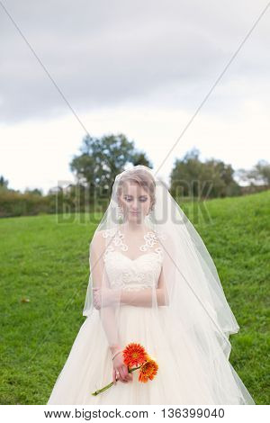 Cheerful bride in wedding day with bouquet of flowers