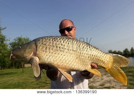 Angler with carp fishing trophy Carp and Fisherman, Carp fishing trophy. Selective focus and shallow Depth of field