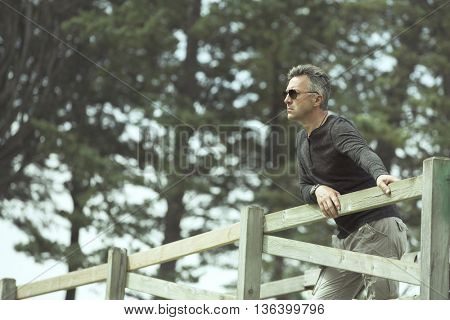Handsome man posing on rural wooden bridge. Outdoor male portrait. Image toned.