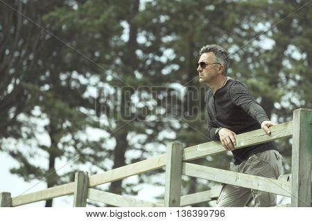 Handsome man posing on rural wooden bridge. Outdoor male portrait. Image toned.