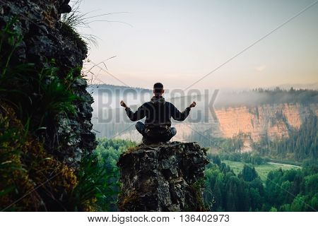 Man sitting on the top of the mountain in yoga pose meeting sunrise.