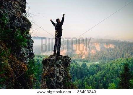 Hiker stands on top of the mountain on sunrise, hands raised up.