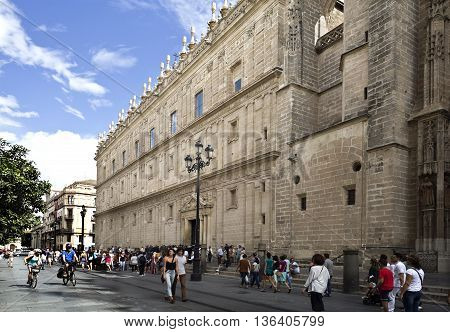 SEVILLE, SPAIN - September 12, 2015: Tourists going along the west facade of the world largest gothic cathedral on September 12, 2015 in Seville, Spain