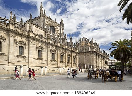 SEVILLE, SPAIN - September 12, 2015: Tourists going along the south facade of the world largest gothic cathedral on September 12, 2015 in Seville, Spain