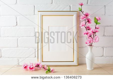 White frame mockup with pink flower bunch. Empty white frame mockup for design presentation. Portrait or poster white frame mockup romantic style.