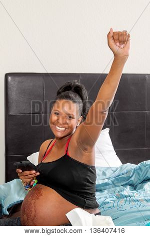 A radiant African American woman at the beginning of her labor throws her arm in the air to celebrate a victorious delivery ahead.